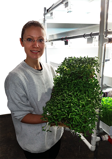 A passion for farming - Maryna holding greens.